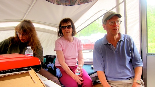 Jim Cluett, W1PID sitting next to Rosemary Landry, KC1AAP inside camper watching Tim Carter, W3ATB trying to log QSOs.