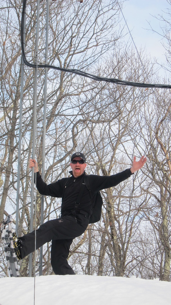 "Mark Persson ""hamming"" it up at the base of the Franklin repeater antenna. Photo credit: Tim Carter, W3ATB"