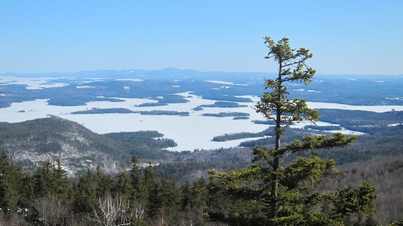 This is the magnificent view to the south. The closer ice-covered lake is Squam Lake where the movie On Golden Pond was shot. The lake farther away is Lake Winnipesaukee and the lake where I live, Lake Winnisquam is a sliver on the right. I can see Mt. Morgan from my deck and back yard. Photo credit: Tim Carter - W3ATB