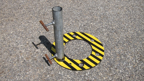 Here's the completed antenna mast support. The yellow and black iron ring is 17 inches in diameter. The galvanized pipe is 17 inches tall and has an ID of 2 inches. Holes were drilled into the side of the pipe so the bolts can secure the mast to eliminate wobble. It's one-half-inch bolt material with a nut welded to the pipe. A small piece of grounding rod is welded to the end of the bolts so you need no tools in the field to secure the antenna mast. Photo credit: Tim Carter - W3ATB