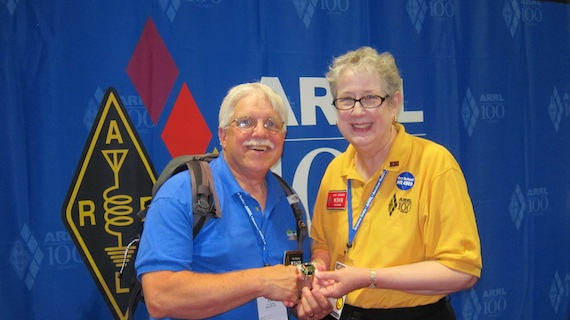 Kay Craigie, current ARRL president, is presenting me with the rare gold ARRL Centennial coin commemorating the historic convention. Photo credit: Carter Craigie