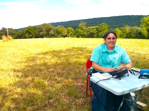 Here's Emily at the small table practicing using the micro Pico paddles to send CW. It only took her about 20 seconds to get comfortable. You can see the Appalachian Trail marker to the left of Emily in the hay field. Photo credit: Tim Carter - W3ATB